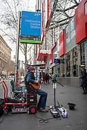 Melbourne, Australia - August 24, 2017: A busker plays guitar and sings on the sidewalk outside Melbourne Central Station on Elizabeth Street