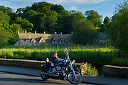 Motorcyclist rests by Arlington Row cottages traditional almshouses in Bibury, Gloucestershire in The Cotswolds, UK