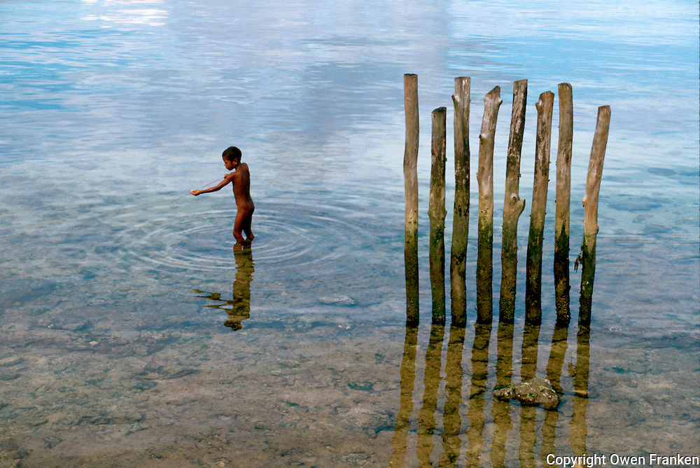 July 1987, Biak Island, Schouten Islands, Indonesia --- A naked young boy fishes with a pointed stick near a row of wooden pilings. Biak Island, Schouten Islands, Indonesia. --- Image by © Owen Franken/CORBIS