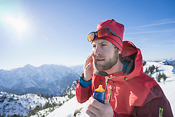 Skier applying sun cream on face