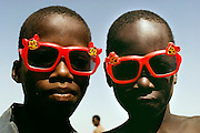 Boys on the banks of the Niger River in Kouakourou, Mali, sport sunglasses made in China. Published in Material World: A Global Family Portrait (1994), pages 12-13.