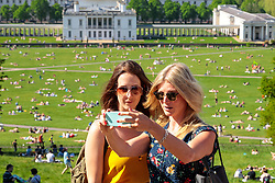 © Licensed to London News Pictures. 07/05/2018. London, UK. Two women take a selfie as thousands of people enjoy the warm weather in Greenwich park on Bank Holiday Monday. Temperatures hit as high as 28.7 degrees C in the capital today, the hottest early May Bank Holiday on record. Photo credit : Tom Nicholson/LNP