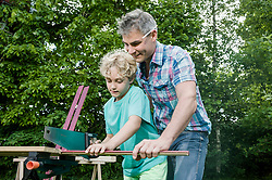 Sawing wood garden father son together
