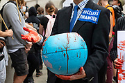 A faceless financier climate activist from Extinction Rebellion holds up a hand soaked in fake blood and a model globe also dripping with fake blood on 27th August, 2021 in London, United Kingdom. The activist group Extinction Rebellion XR are planning actions of disruption for two weeks straight beginning on August 23rd, 2021 in an effort to bring awareness and priority to the global climate emergency in advance of the COP 26 Summit which will be held in Glasgow later this year.