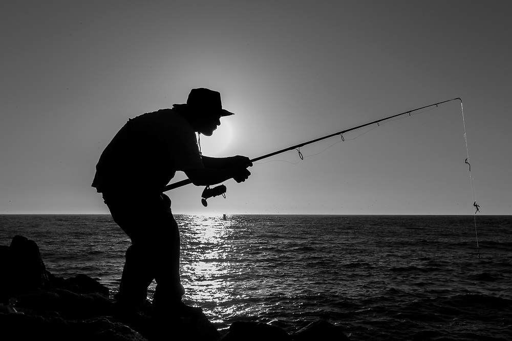 A man fishes for rock cod in Moss Landing, Calif. on Sept. 30, 2021.