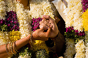 At a Hindu wedding, the bride and groom clasp each others hands as the groom receits Vedic hymns to bless their marriageand any future children they may have, Neemrana Fort Palace, Rajasthan, India.