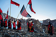 Men with flags and traditional wool clothing from Paucartambo village go up to the sacred mountain Sinaqara to worship to all the mountains or Apus, during the celebration of the Lord of Qoyllur Rit'i (The Lord of the Shining Snow) in Cusco, Peru. By the climate change the glacier is retiring, now in the place of the ritual there isn't snow, for them, snow is sacred and an important part of the celebration.