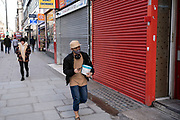 People wearing face masks walk past shuttered closed shops along the shopping district Oxford Street which is largely empty of shoppers as the national coronavirus lockdown three continues on 28th January 2021 in London, United Kingdom. Following the surge in cases over the Winter including a new UK variant of Covid-19, this nationwide lockdown advises all citizens to follow the message to stay at home, protect the NHS and save lives.