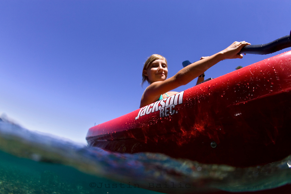 Young girl kayaking near DL Bliss State Park on Lake Tahoe, CA.