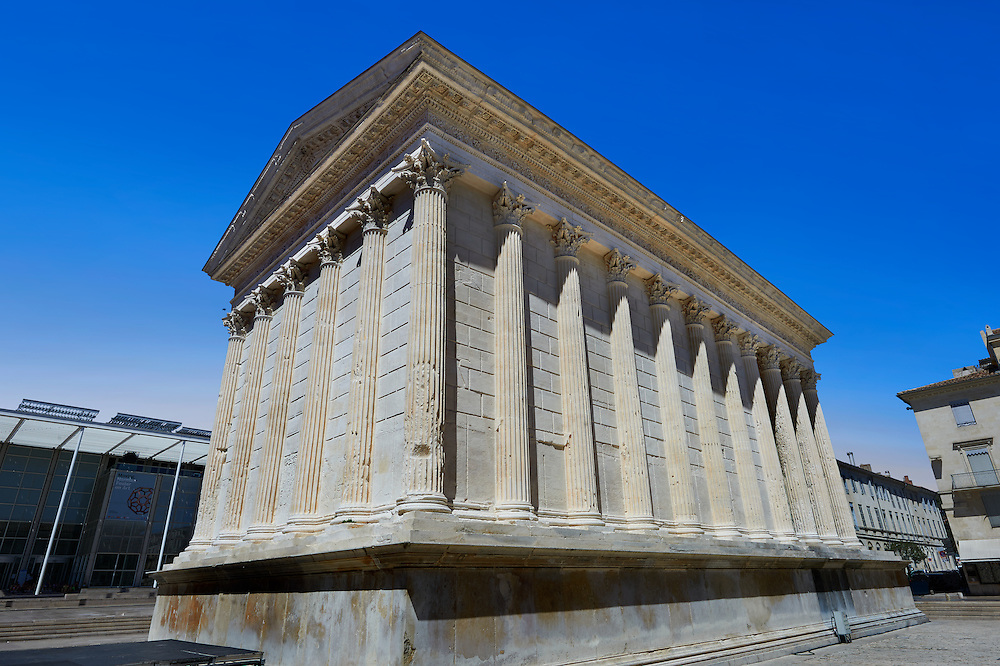 Maison Carrée, a ancient Roman temple built around 4-7 AD and dedicated to Julius Caesar, the best preserved example of a Roman temple,  Nimes, France . In about 4-7 AD, the Maison Carrée was dedicated or rededicated to Gaius Caesar and Lucius Caesar, grandsons and adopted heirs of Augustus who both died young. The Maison Carrée is a classic example of Vitruvian architecture as it is nearly an exact replica of a Tuscan style Roman temple described in the writings of the famous architect Vitruvius. Raised on a 2.85 m high podium, and at 26.42 m by 13.54 m forming a rectangle almost twice as long as it is wide, the temple dominated the forum of the Roman city of Nîmes. .<br /> <br /> Visit our ROMAN ART & HISTORIC SITES PHOTO COLLECTIONS for more photos to download or buy as wall art prints https://funkystock.photoshelter.com/gallery-collection/The-Romans-Art-Artefacts-Antiquities-Historic-Sites-Pictures-Images/C0000r2uLJJo9_s0