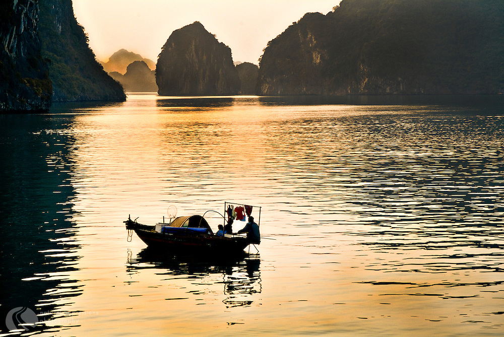 Morning begins on Ha Long Bay with a beautiful sunrise, as industrious fishermen float its waters using ancient handmade boats.