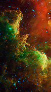 This swirling landscape of stars is known as the North America nebula. Spitzer.