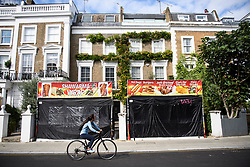 © Licensed to London News Pictures. 25/08/2018. London, UK. A woman cycles past takeaway food stands in the front garden of a property in Notting Hill, West London ahead of the 2018 Notting Hill Carnival which starts tomorrow (Sunday). Up to 1 million people are expected to attend this weekend's event that is one of the worlds largest street festivals. Photo credit: Ben Cawthra/LNP