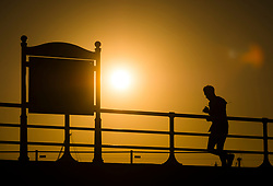 © Licensed to London News Pictures.10/10/2018. Aberystwyth, UK. A man jogging in the sun as autumn dawn breaks over Aberystwyth harbour on the west wales coast, heralding a day of warm sunshine for much of the UK.  Photo credit: Keith Morris/LNP