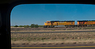 A BNSF (Burlington Northern Santa Fe) railroad freight train passes by along rural I-20 in west Texas, USA framed in a Mini Cooper window