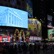 A panoramic view of Time Square, New York at night time. Times Square is the major commercial intersection in Midtown Manhattan, New York City, at the junction of Broadway and Seventh Avenue and stretching from West 42nd to West 47th Streets. Time Square, New York, USA. 27th April 2012. Photo Tim Clayton.Note to Editors. This image is a composite of three images taken a split second apart and merged in editing.