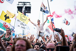 Festival goer holding a red flare is held above the Pyramid Stage crowd on day 4 of Glastonbury 2019, Worthy Farm, Pilton, Somerset. Picture date: Saturday 29th June 2019.  Photo credit should read:  David Jensen/EmpicsEntertainment
