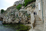 Children on steps, buildings set in stone outcrop, beneath Fortress Lovrijenac (Fort of Saint Lawrence), Dubrovnik old town, Croatia