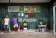 Men sell newspapers and cigarettes outside a closed beer shop window in Vanimo, Papua New Guinea (2017)