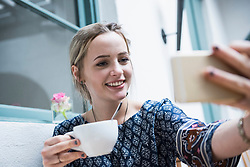 Young woman holding coffee cup and taking self portrait at restaurant