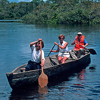 South America, Peru, Amazon River. Rowing in a dug out canoe on the Amazon