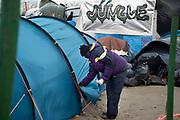 France , Calais, camp for refugees known as 'The Jungle'. November 2015. A man closes his tent. Behind him the word 'Jungle' is written on a tent.