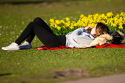 A woman sunbathes on the lush grass as crowds enjoy the unseasonably warm and sunny weather in Regents Park, London. London, February 26 2019.