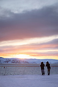 Couple looking at sun rising over scenic snow-capped mountain range, Havoysund, Norway
