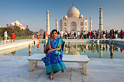 Indian tourist sits on Diana bench at The Taj Mahal mausoleum southern view with reflecting pool, Uttar Pradesh, India