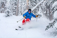 An expert powder skier enjoying a fresh line on newly fallen snow on a cold morning in Arizona
