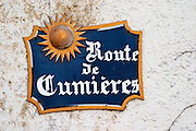A blue street sign on a white wall in the village that indicates the road to the next village Cumieres and a sun, the village of Hautvillers in Vallee de la Marne, Champagne, Marne, Ardennes, France