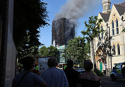 Local residents in Lancaster Road watch as smoke billows from a fire that has engulfed the 24-storey Grenfell Tower in west London.