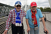 Twin brothers who support opposing football teams walking together across the Golden Jubillee Bridge next to Hungerford Bridge. The brother on the left supports Chelsea FC and his brother on the right supports Arsenal Football Club. London, UK.