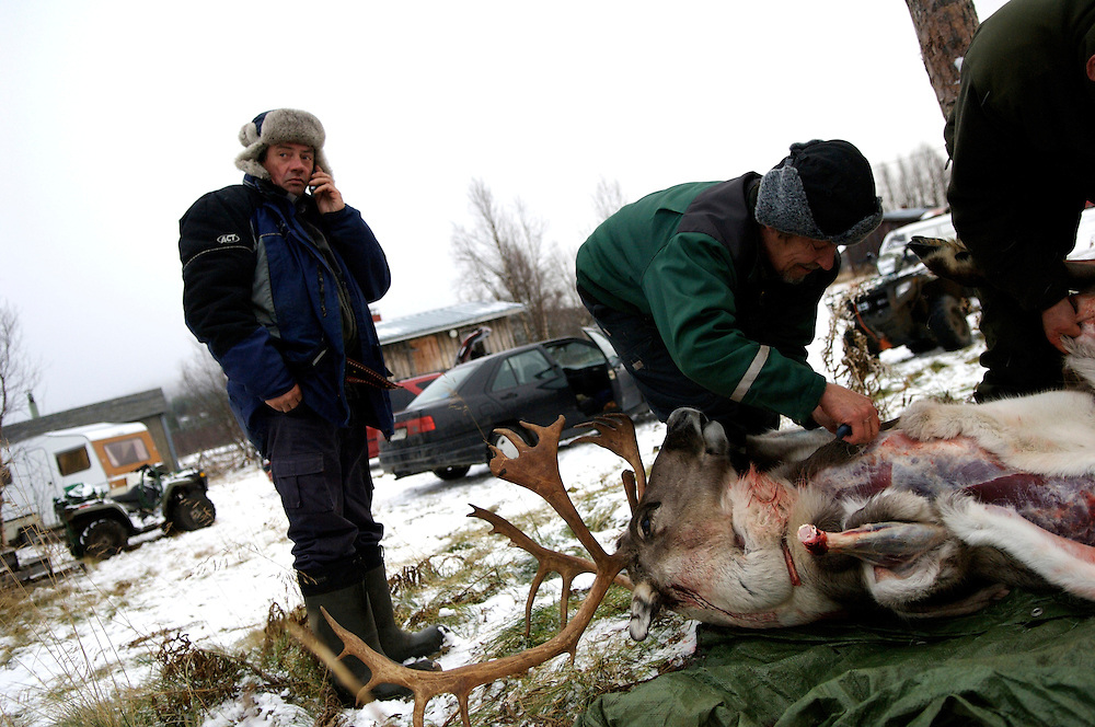Veggai (left), 58, a Sami elder and once champion lasso thrower, confers with his daughter as to how many reindeer she would like him to slaughter.  This day marked the first snowfall, roundup, and slaughter of the year.  Taneli Nakkalajarvi, 28, takes a smoke break from slaughtering reindeer.  He is one of five herders who slaughter, earning only £.40 per reindeer.  Despite the inhospitable Arctic climate reindeer herding has been the livelihood of the Sami for hundreds of years, but amid the economic, technological, and environmental problems of modern society their indigenous culture must increasingly reconcile these radical changes in order to preserve age-old traditions, customs, and mores.