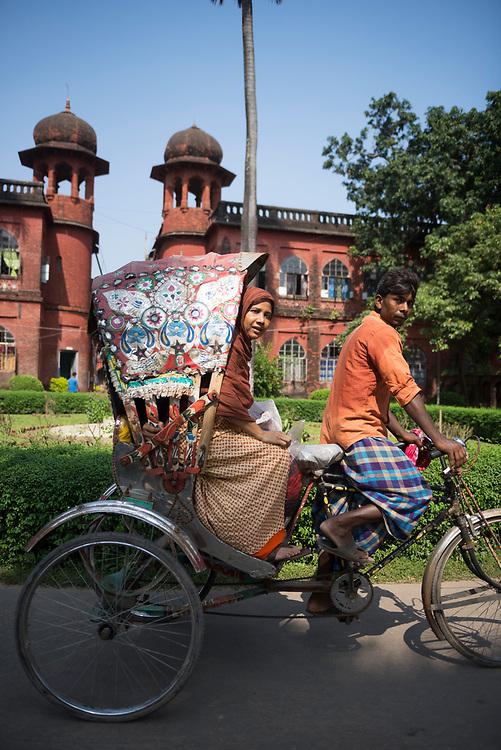 A rickshaw with passenger moves down a street at the University of Dhaka campus in Dhaka, Bangladesh.