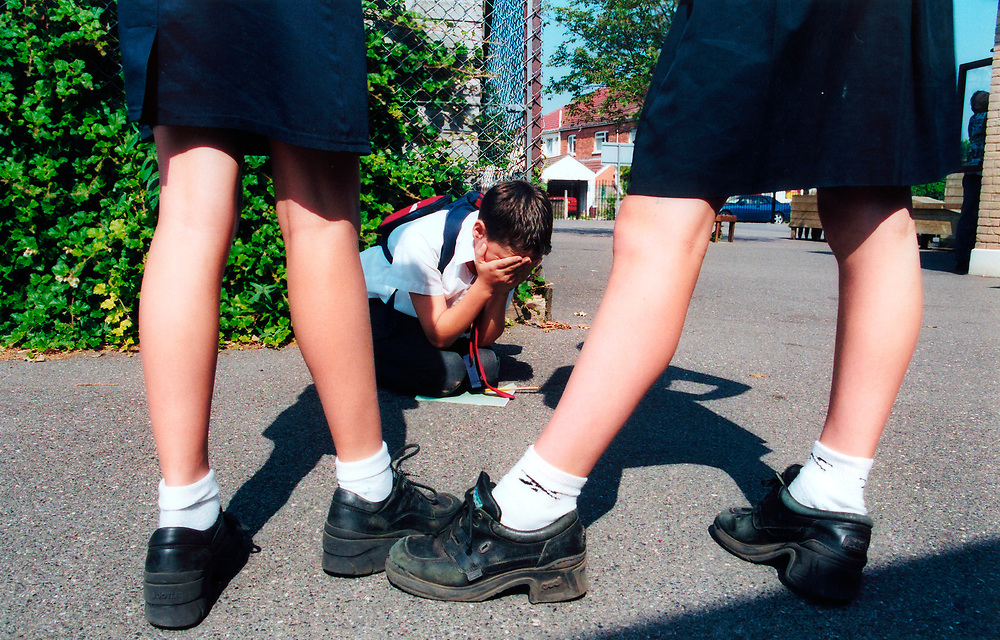 Bullying at school - girls standing over boy who is crying on the playground floor; UK. POSED BY MODELS