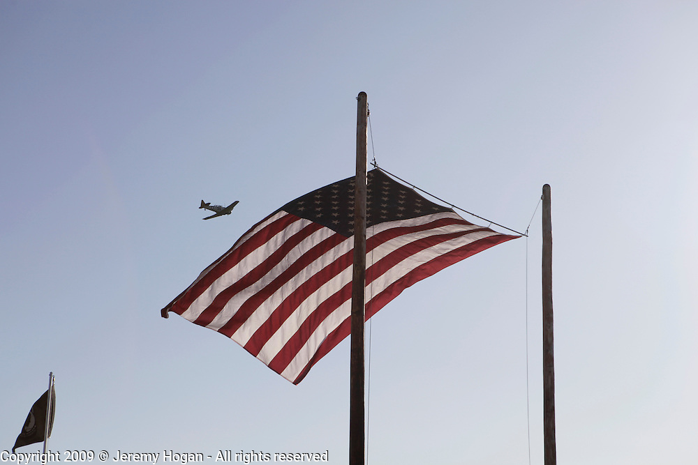 A WWII era plane flies past a large American Flag during the Vietnam Veterans gathering in Kokomo, Indiana for the 2009 reunion.