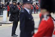 London 17/4/13 - Armed policeman and guardsman in before the funeral of Margaret Thatcher. Draped in the union flag and mounted on a gun carriage, the coffin of ex-British Prime Minister Baroness Margaret Thatcher's coffin travels along Fleet Street towards St Paul's Cathedral in London, England. Afforded a ceremonial funeral with military honours, not seen since the death of Winston Churchill in 1965, family and 2,000 VIP guests (incl Queen Elizabeth) await her cortege.