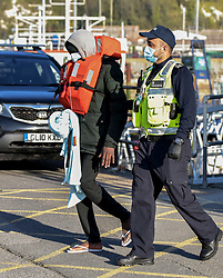 DATE CORRECTION © Licensed to London News Pictures. 13/04/2021. Dover, UK.A migrant is helped ashore by a Border Force officer at Dover Harbour in Kent after crossing the English Channel. Home Secretary Priti Patel has pledged an overhaul of asylum seeker rules, with refugees having their claim assessed based on how they arrive in the UK. Photo credit: Stuart Brock/LNP