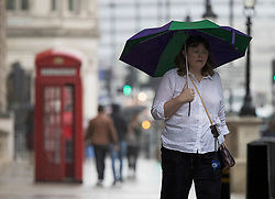 © Licensed to London News Pictures. 10/09/2021. A woman shelters form the rain underneath an umbrella in Westminster, central London.. Thunderstorms are expected across parts of the UK following a period of warm weather earlier this week. Photo credit: Ben Cawthra/LNP