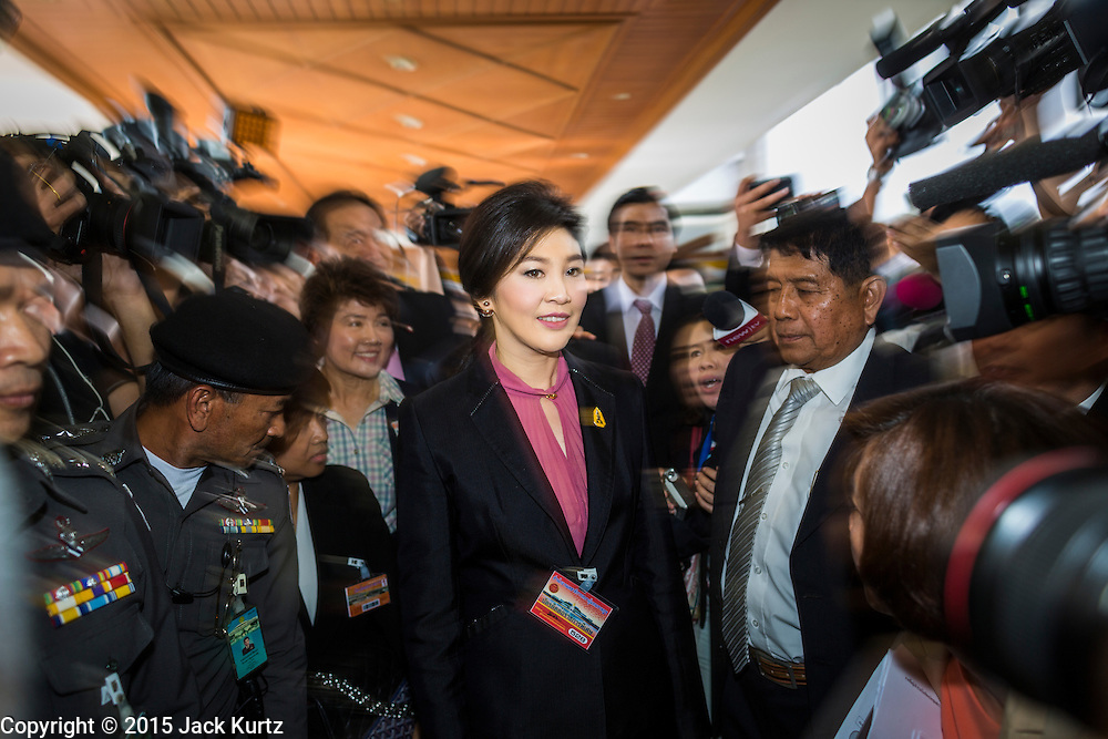 """09 JANUARY 2105 - BANGKOK, THAILAND:  YINGLUCK SHINAWATRA, former Prime Minister of Thailand, walks through a crowd of supporters to a waiting car after presenting her defense during her impeachment at the National Legislative Assembly. Thailand's military-appointed National Legislative Assembly began impeachment hearings Friday against former Prime Minister Yingluck Shinawatra. If she is convicted, she could be forced to stay out of politics for five years. During her defense, Yingluck questioned the necessity of her impeachment, saying, """"I was removed from office, the equivalent of being impeached, three times already, I have no position left to be impeached from."""" A decision on her impeachment is expected by the end of January.   PHOTO BY JACK KURTZ"""