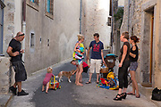 Families meeting up in the hot, summer street, 19th July 2015, Lagrasse France.