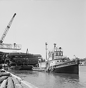 "Ackroyd 07152-40. ""Sause Bros. aerials. September 23, 1956"" tug Go-Getter pulling barge loaded with logs."