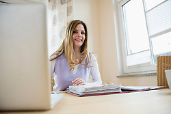 Woman with laptop and folder at home