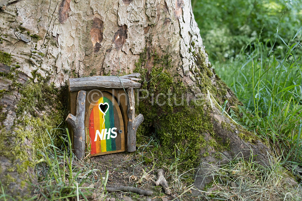 Tiny home made wooden door attached to a tree, painted in rainbow colours and with a heart shaped hole in support of NHS workers during the Coronavirus pandemic in Highbury Park, Kings Heath on 22nd May 2020 in Birmingham, England, United Kingdom. Coronavirus or Covid-19 is a new respiratory illness that has not previously been seen in humans. While much or Europe has been placed into lockdown, the UK government has put in place more stringent rules as part of their long term strategy, and in particular social distancing.