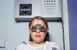 Young girl having eyes tested at an opticians,