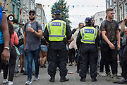 A heavy police presence during the Notting Hill Carnival on the 27th August 2018 in London in the United Kingdom. The Notting Hill Carnival is an annual event held over two days of the August Bank Holiday weekend. It has taken place in London since 1966 on the streets of Notting Hill, in the Royal Borough of Kensington and Chelsea and the City of Westminster.