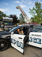 Colton Watson takes a test drive from the drivers seat of the Belmont cruiser during Belmont's National Night Out at the Belmont Mill Tuesday evening.  (Karen Bobotas/for the Laconia Daily Sun)