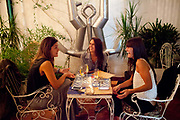 Young women enjoying a drink in Rey de Copas bar, Palermo, Buenos Aires, Federal District, Argentina.