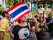 """09 JUNE 2013 - BANGKOK, THAILAND:   A member of the White Mask protest movement waves a Thai flag on the plaza in front of Central World in Bangkok. The White Mask protesters wear the Guy Fawkes mask popularized by the movie """"V for Vendetta"""" and the protest groups Anonymous and Occupy. Several hundred members of the White Mask movement gathered on the plaza in front of Central World, a large shopping complex at the Ratchaprasong Intersection in Bangkok, to protest against the government of Thai Prime Minister Yingluck Shinawatra. They say that her government is corrupt and is a """"puppet"""" of ousted (and exiled) former PM Thaksin Shinawatra. Thaksin is Yingluck's brother. She was elected in 2011 when her brother endorsed her.     PHOTO BY JACK KURTZ"""